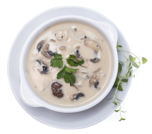 Fresh Mushroom Soup topped with some herbs isolated on white background